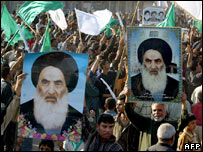 Iraqis hold banners of Ayatollah Sistani at a demonstration in Sadr City