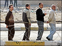 Men queue to cast their vote for the Iraqi parliamentary elections, which will select a National Assembly that will serve for four years, at the al-Maali elementary school polling station in Mosul in