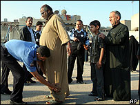 Iraqi men go through security check prior to voting at an election centre at Al-Sadr city, east of Baghdad, Iraq, Thursday, Dec. 15, 2005