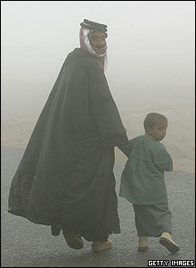 Father and son walk through the fog to vote in al-Zubayr, southern Iraq