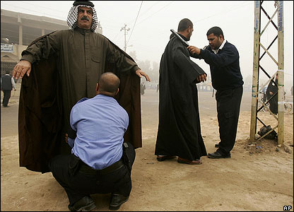 Iraqi men are searched before voting in al-Zubayr, southern Iraq