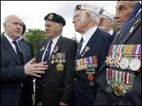 Dr John Reid (L) talks with veterans