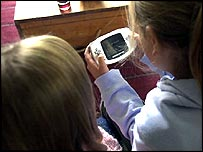 girls playing handheld game
