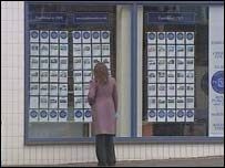 Woman looking in estate agents window