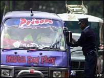 Kenyan police officer next to minibus taxi