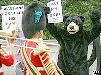 A protester dressed as a bear demonstrates outside Buckingham Palace as a detachment of the Royal Guards pass by