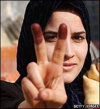 Iraqi woman displays inked finger, showing she has voted