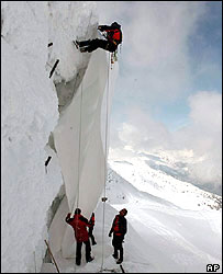 Workers cover parts of the Gurschen glacier with plastic sheeting