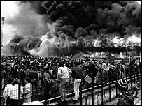 Fans look on as the fire engulfs the main stand