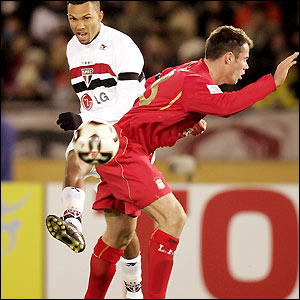 Amoroso squeezes a shot past defender Jamie Carragher