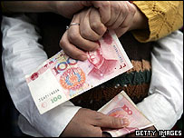Hands holding yuan notes