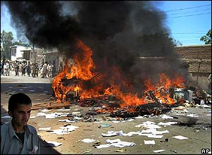 A car burns in the street as university students protest in the streets in Jalalabad, Afghanistan