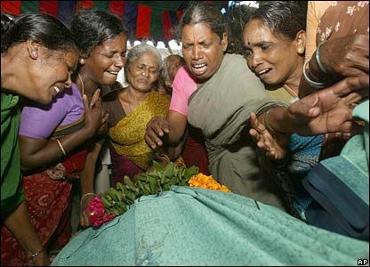 Relatives mourn near the body of a woman killed in the stampede