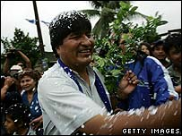Evo Morales arrives amid confetti to vote with coca branch in hand