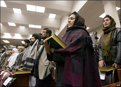 Afghanistan's new lawmakers hold copies of the Koran during their swearing-in ceremony in Kabul