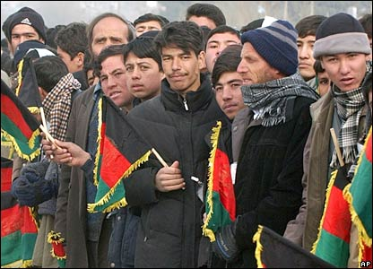 Afghans hold national flags outside the parliament building