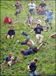 Participants in Gloucestershire's annual cheese rolling competition tumble down the hill