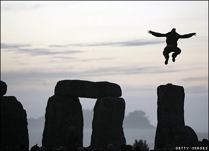 A reveller leaps from the top of Stonehenge during summer solstice celebrations