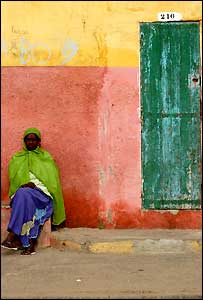 A woman sitting by a colourful house and doorway in St Louis, Senegal (Copyright BBC News website reader Michelle Donnelly-Bray)