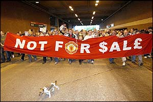 A large number of Man Utd supporters holding a banner pass under the tunnel at the stadium