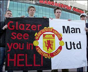 Four Man Utd fans hold a provocative flag up informing Glazer that his takeover at the football giants will not be smooth