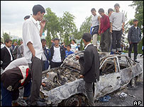 People stand on burned-out car, Andijan, 13/5/05