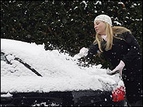 A woman scrapping snow and ice off her car