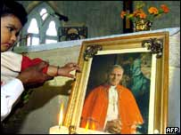 Child touching picture of Pope John Paul II