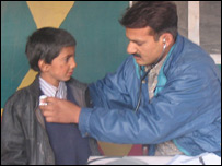 Doctor at Jamat Ud Dawa Field Hospital examining child
