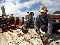Workers in Aceh fix a damaged fishing boat