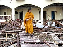 Thai Buddhist monk walks through debris at the Similan Beach and Spa Resort Hotel in Khao Lak