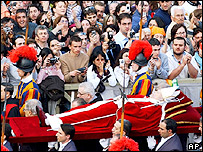 The Pope's body is carried past the crowds of mourners in St Peter's Square