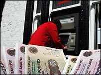 A woman uses an automatic telling machine at The Clydesdale Bank