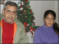 Nasim Bannoura [left] with one of his daughters in front of their Christmas tree in Bethlehem