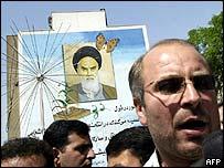 Mohammed Baqer Qalibaf (r) in front of portrait of Ayatollah Khomenei