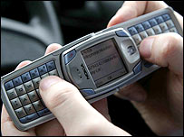 Photo of a mobile handset with a full keyboard being used for texting