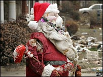 A damaged Santa standing in front of a home destroyed by Hurricane Katrina