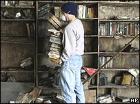 A volunteer collects books from the flood-damaged library at Beth Israel synagogue in New Orleans