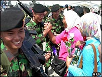 Indonesian military shake hands with Acehnese women as they pull out of the province