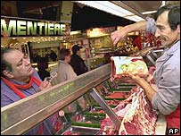 French butcher shows meat to a customer