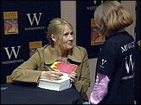 JK Rowling signing a book for a young fan