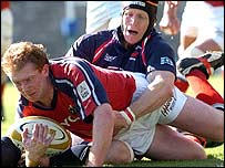 Munster's Anthony Horgan scores the opening try despite the tackle by Llanelli Scarlets' Simon Easterby