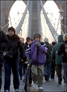 Commuters walk over the Brooklyn Bridge