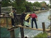 Residentes uzbecos cruzan un puente sobre el río en su intento de llegar a Kirguizistán