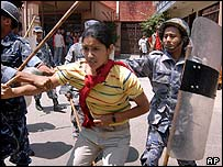 Riot police detain a student activist in Kathmandu on 15 May