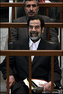 Former Iraqi President Saddam Hussein smiles during court proceedings against him and his co-defendants in the resumption of their trial December 21, 2005 in Baghdad, Iraq.