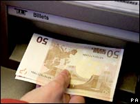 A person withdraws 50-euro notes from a cash machine in France. File photo