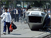 Boy walks past overturned car in Andijan, Uzbekistan