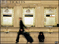 A commuter walks past another sleeping under ticket windows in New York