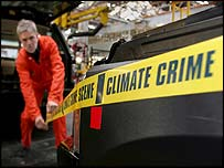 Greenpeace volunteer wrapping 'climate crime scene' tape around a half-built Range Rover